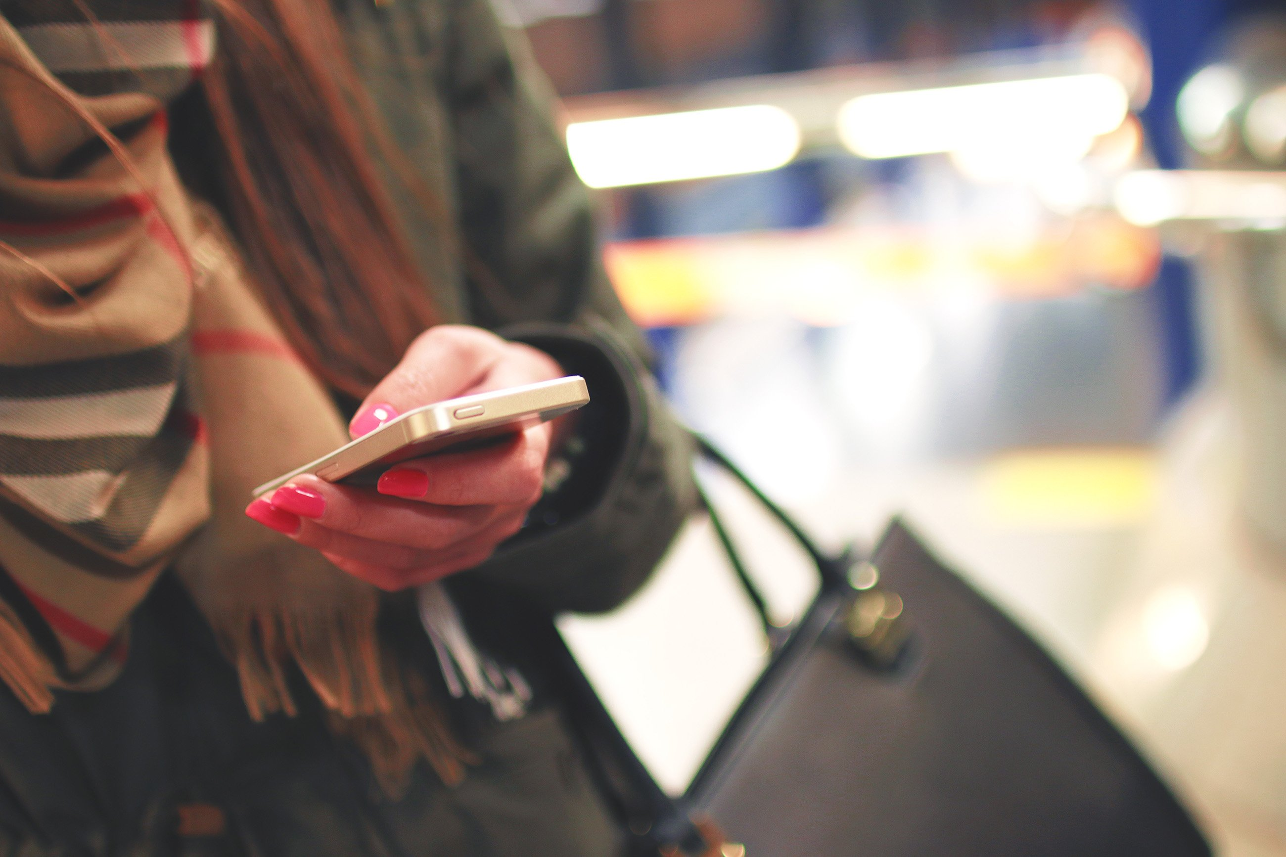 woman texting with bag and scarf